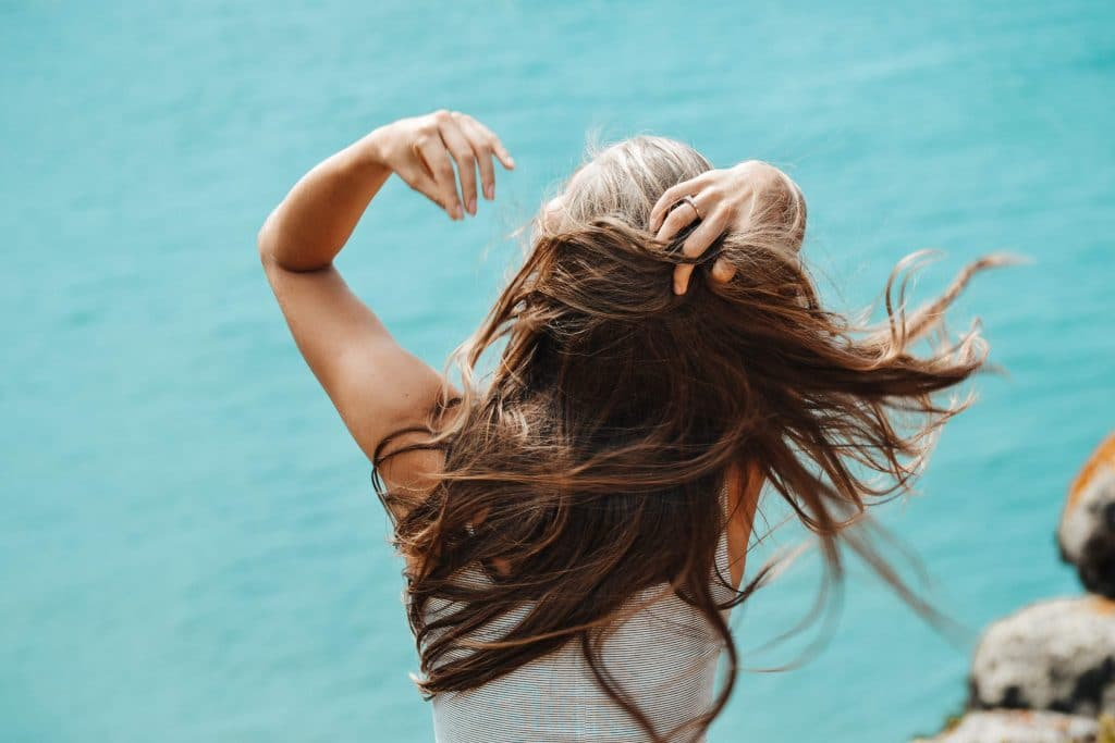 Back view photo of woman in white sleeveless shirt running her fingers through her hair