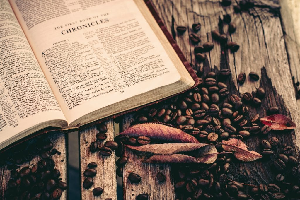 Bible on rustic wood covered with coffee beans.