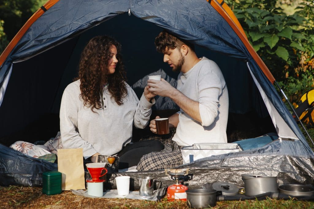 Couple of travelers with coffee in tent
