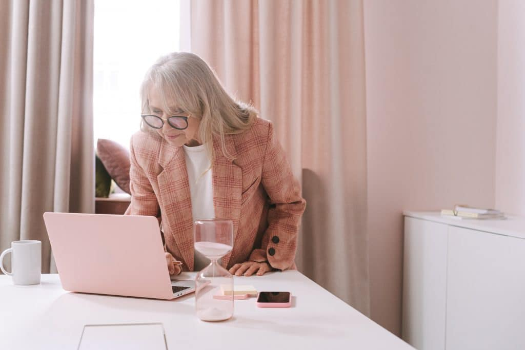 Woman in brown coat sitting by the table using macbook