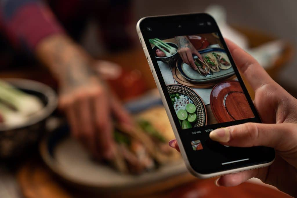A person taking photo of the food on the table